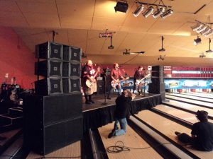 The band Bowling For Soup plays on a stage built on top of a bowling alley