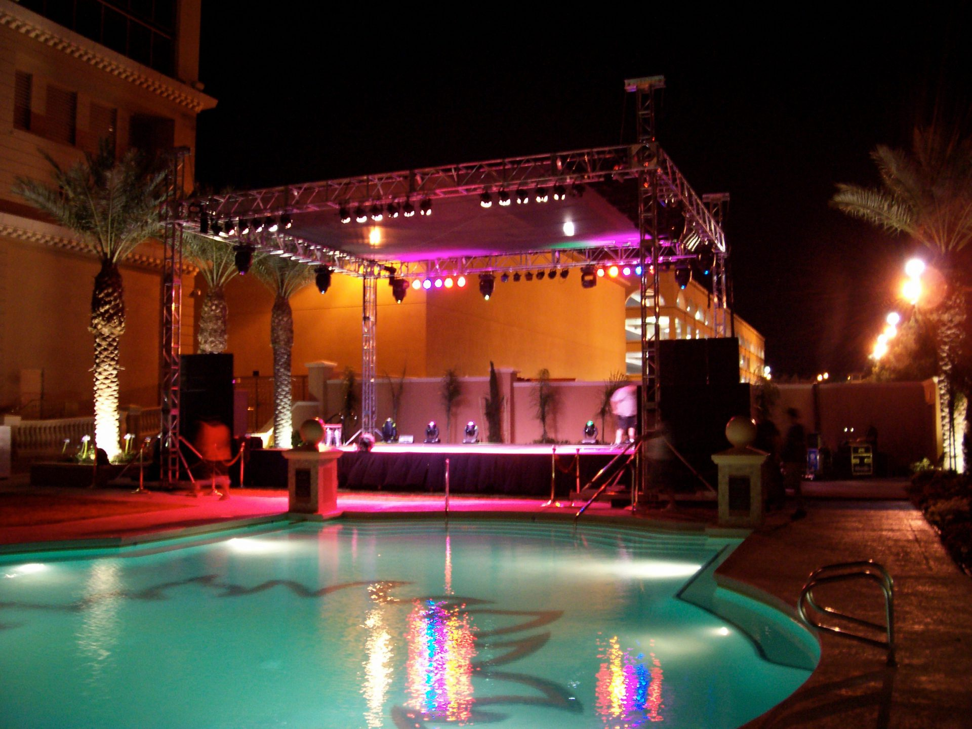 Beautiful lighted stage by a hotel swimming pool, ready for a concert
