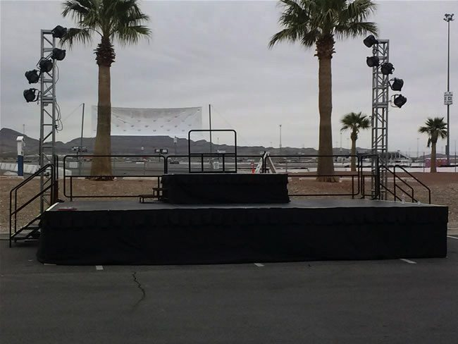 a small stage setup on a parking lot, with lighting trees on each side