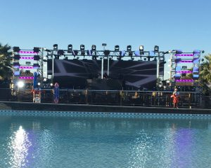 Large stage sits at the edge of a massive swimming pool