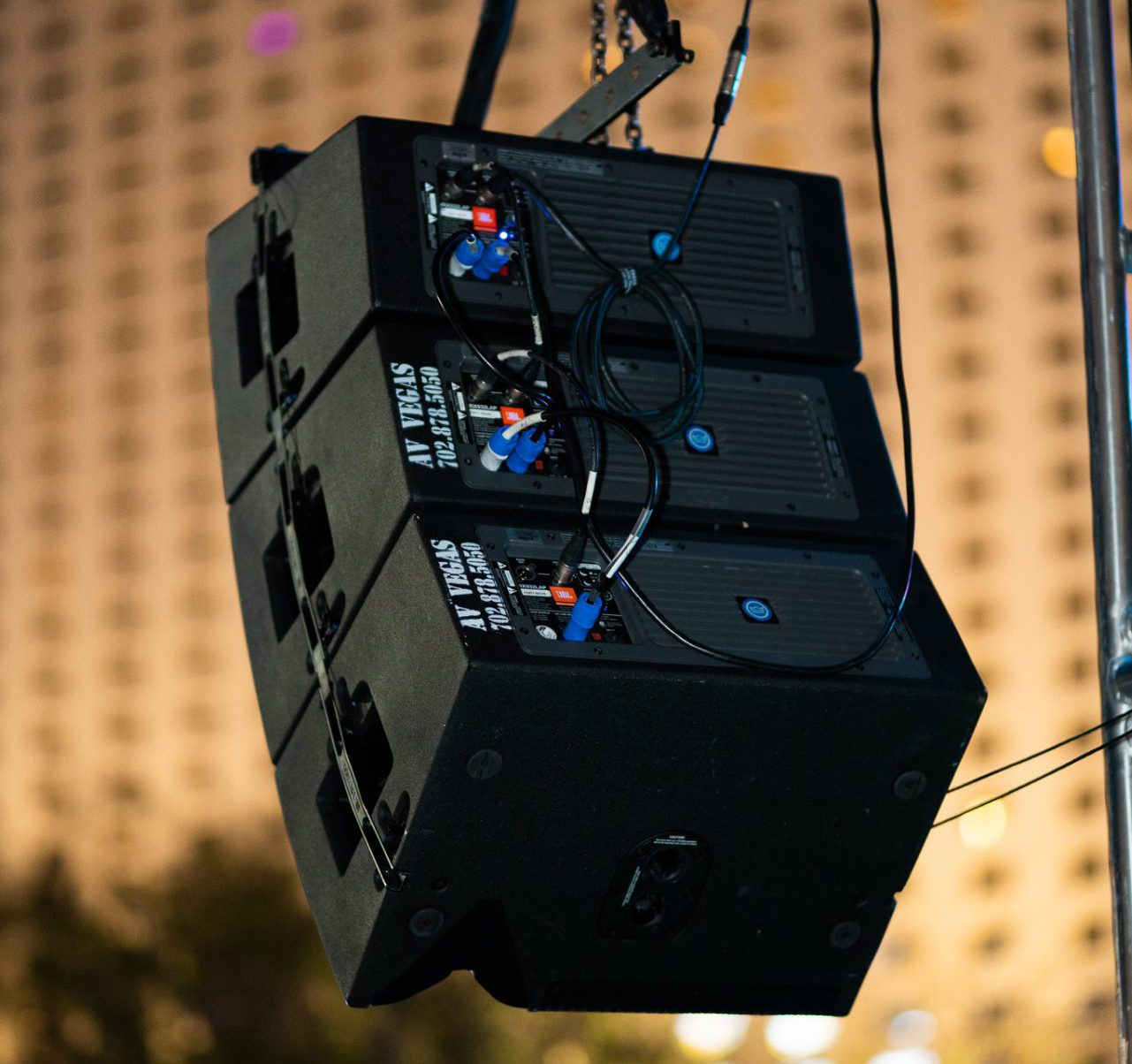 Rear view of JBL VRX Speakers hanging in the air, Las Vegas hotel in background.