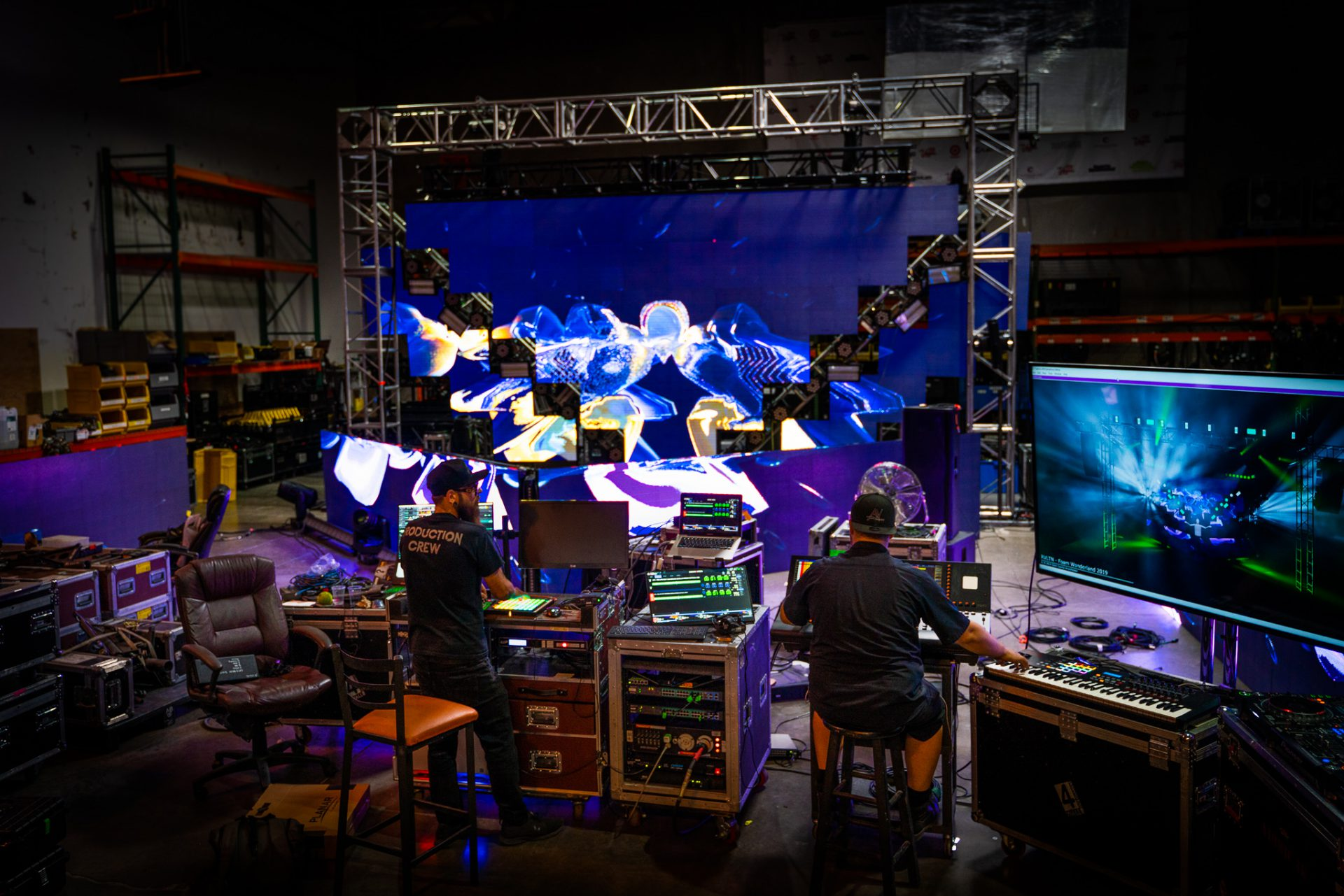 two team-members work side by side programming a video wall and lighting structure for a rave